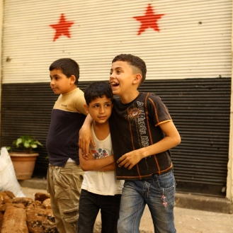 In the Lebanese neighborhood of Bab al-Tabbaneh, people use sandbags to shield their buildings from sniper fire. These children stand in front of a garage painted with the opposition-adopted Syrian flag, showing their support for the rebels.