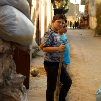 Children take a break from building the sandbag walls in the Lebanese neighborhood of Jabal Mohsen.