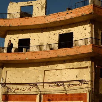 A bullet-ridden apartment building in Jabel Mohsen is almost completely abandoned and is being used as a sniper lookout. by Saskia de Melker